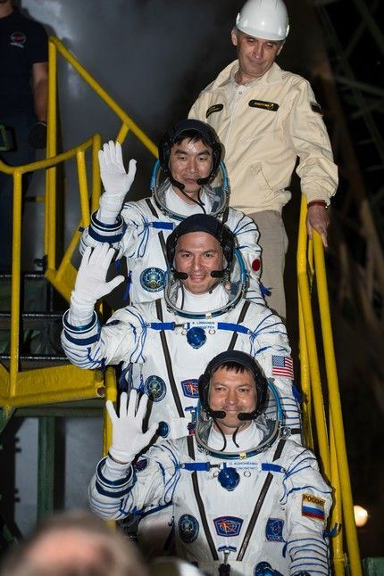 Expedition 44 Flight Engineer Kimiya Yui, of the Japan Aerospace Exploration Agency (JAXA), top; Flight Engineer Kjell Lindgren of NASA, center, and Soyuz Commander Oleg Kononenko of the Russian Federal Space Agency (Roscosmos), bottom, wave farewell prior to boarding the Soyuz TMA-17M spacecraft for launch, Thursday, July 23, 2015 at the Baikonur Cosmodrome in Kazakhstan. Kononenko, Lindgren, and Yui will spend the next five months aboard the International Space Station. Photo Credit: (NASA/Aubrey Gemignani)